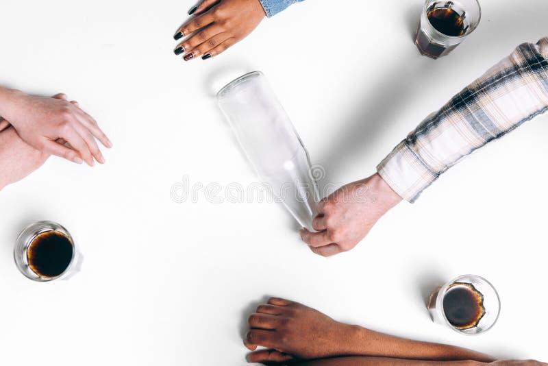 Quatre amis jouent la rotation le jeu de bouteille, configuration plate photo stock