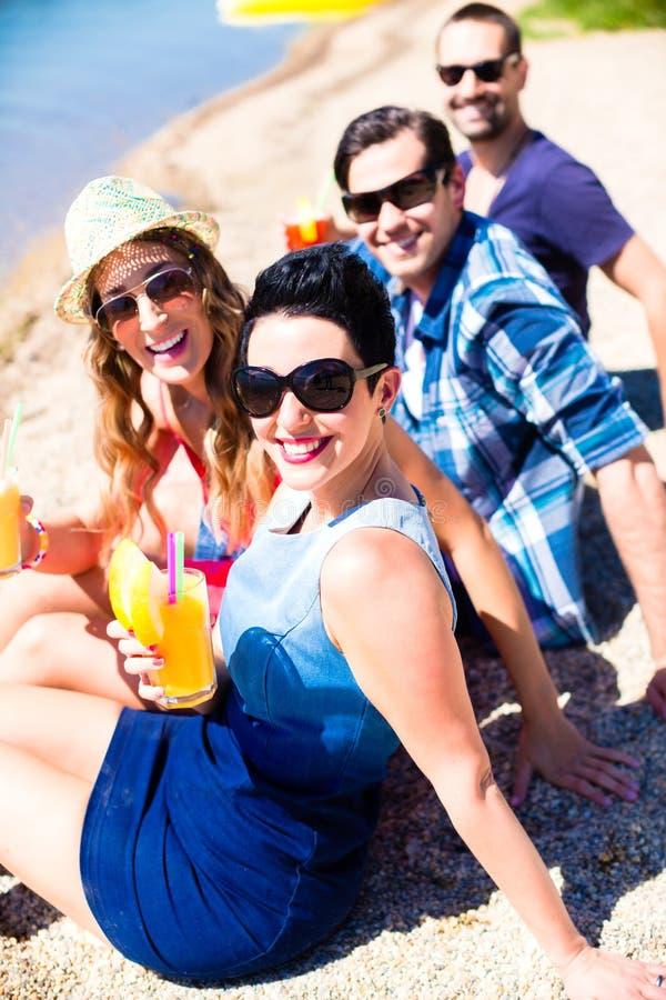 Quatre amis s'asseyant sur la plage de lac avec des cocktails photos stock