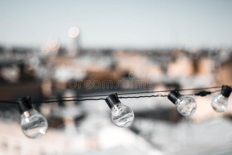 Quatre ampoules en verre contre les toits des maisons et du ciel L'ampoule sur le dessus La vue ? partir du dessus Fin vers le ha photos stock