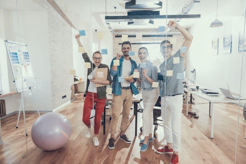 Quatre associés de sourire apprécient leur travail ensemble dans le bureau photo libre de droits