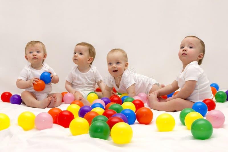 Quatre bébés drôles mignons s'asseyant sur la couverture blanche et jouant les boules colorées Partie infantile images stock