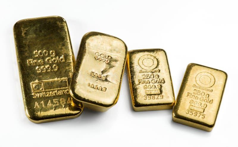 Quatre barres d'or moulées de poids différent sur le blanc images stock