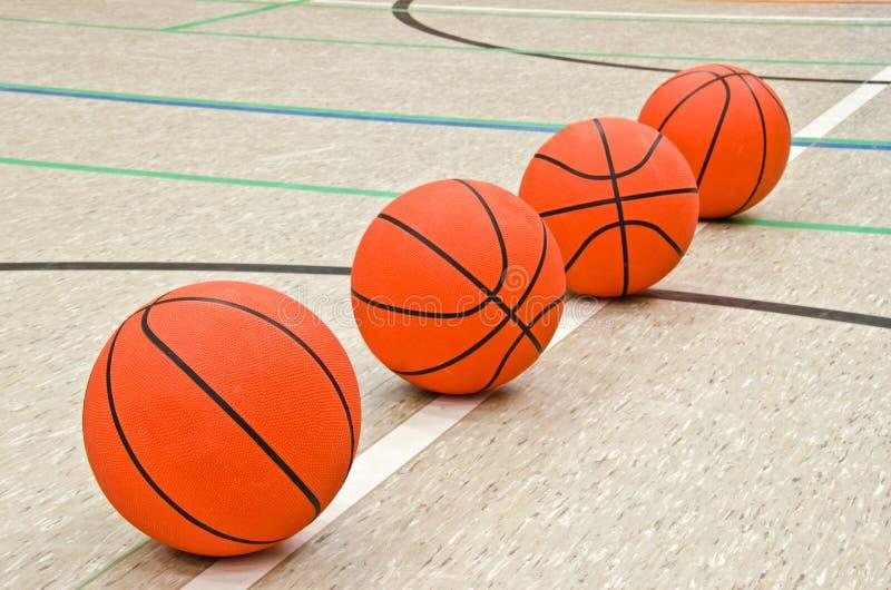 Quatre basket-balls sur le plancher image stock