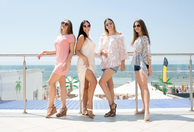 Quatre beaux, différentes, jeunes filles se tiennent à l'arrière-plan d'un hôtel chic, plein-longueurs Beaux, charmants jeunes photos libres de droits