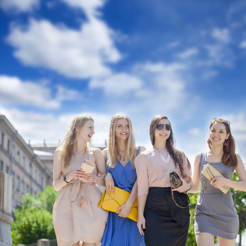 Quatre belles femmes de mode marchant sur la rue image stock