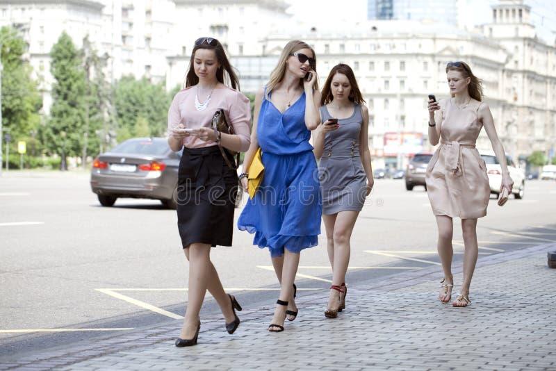 Quatre belles filles de mode marchant sur la rue photos libres de droits