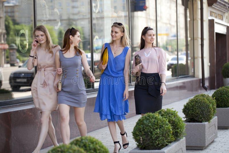 Quatre belles filles de mode marchant sur la rue photographie stock libre de droits