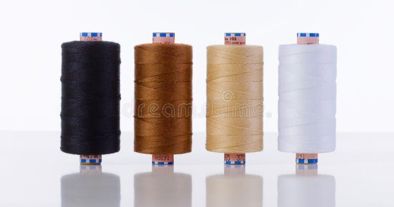 Quatre bobines de fil de couture de différentes couleurs images stock