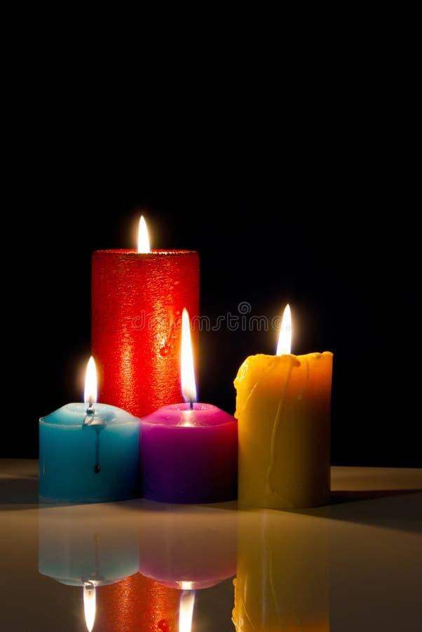Quatre bougies brûlantes colorées photos libres de droits