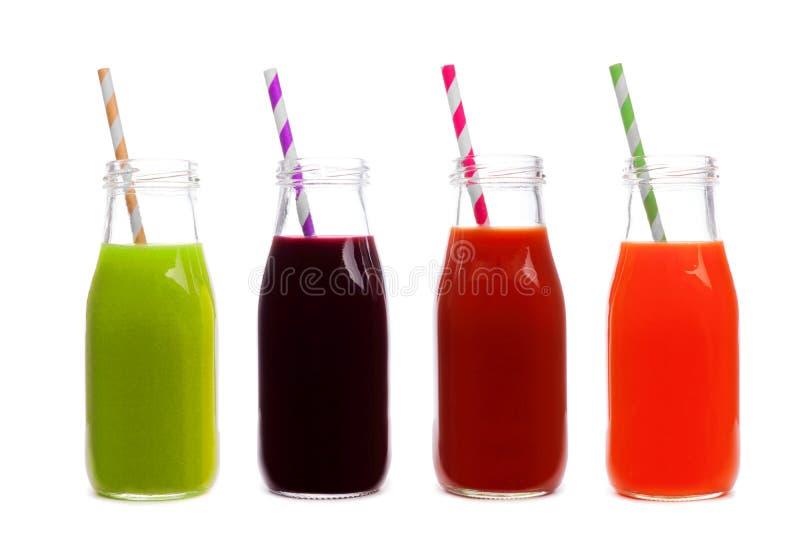 Quatre bouteilles de jus de légumes, de verts, de betterave, de tomate, et de carotte, d'isolement image libre de droits