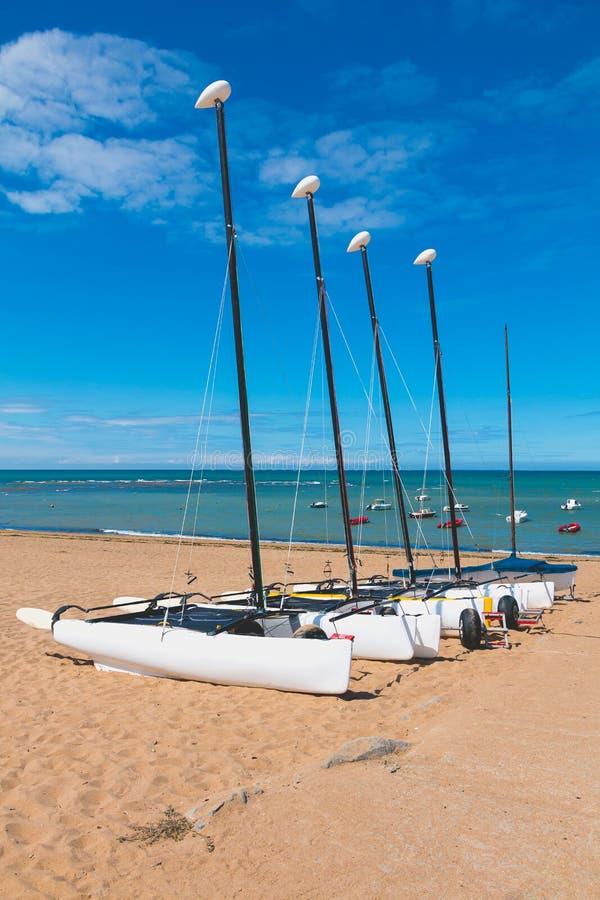 Quatre catamarans se sont étendus sur le sable par la mer photographie stock libre de droits