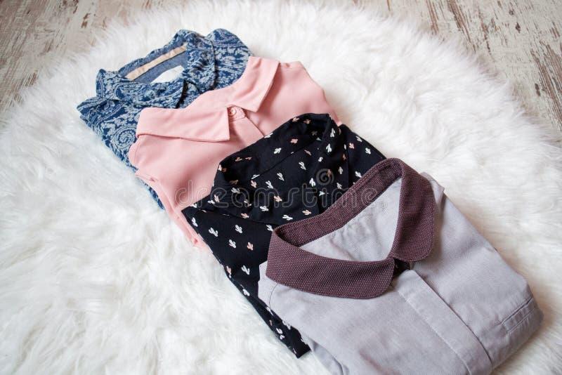 Quatre chemises différentes sur la fourrure blanche, assortiment Concept de mode photographie stock