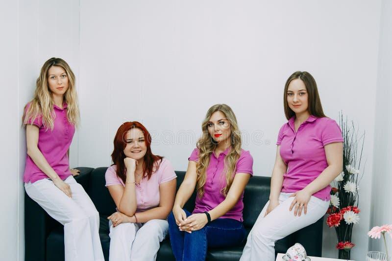 Quatre coiffeurs posant dans le salon de coiffure images libres de droits