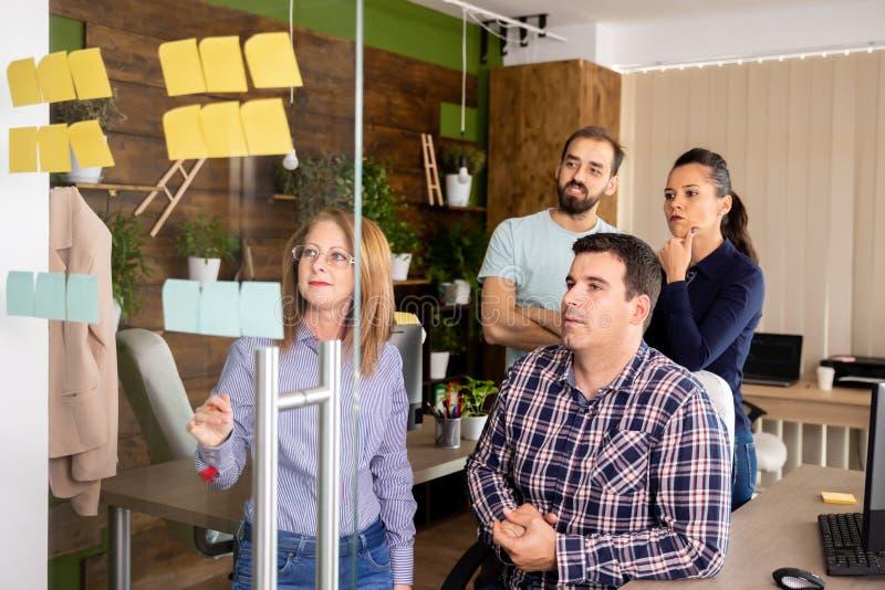 Quatre collègues discutent quelques données du projet image libre de droits