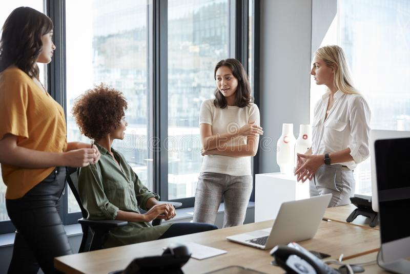 Quatre collègues féminins dans la discussion à un bureau dans un bureau créatif, longueur de trois-quarts images stock