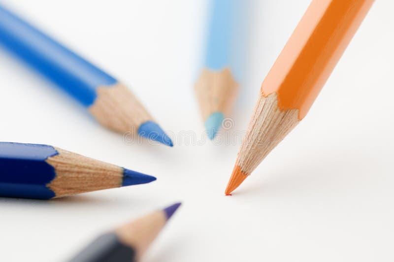 Quatre crayons bleus et d'une orange images stock