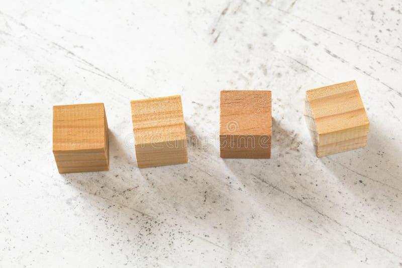 Quatre cubes en bois en blanc sur le panneau de ciment blanc photographie stock