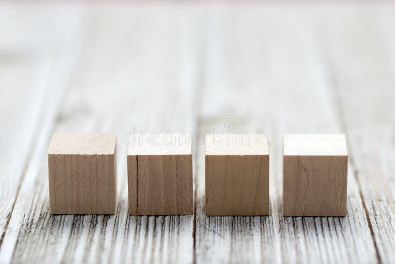 Quatre cubes en bois en jouet sur le fond en bois gris images libres de droits
