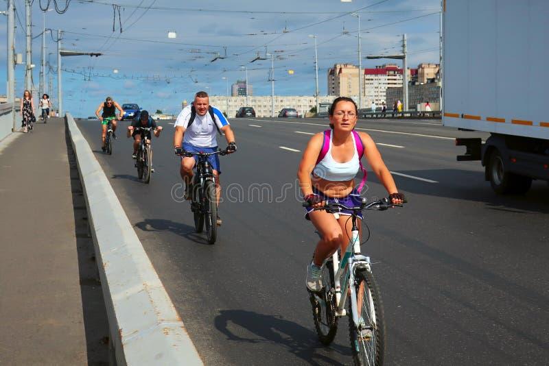 Quatre cyclistes montant le long du bord de la route photo stock