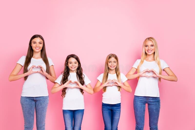 Quatre dames faisant le symbole de chiffre de coeur avec des mains portent le fond rose d'isolement par équipement occasionnel image libre de droits