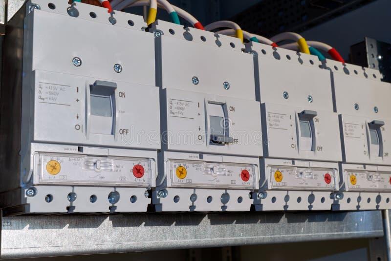 Quatre disjoncteurs de puissance sont fixés dans le Cabinet électrique dans la ligne images stock