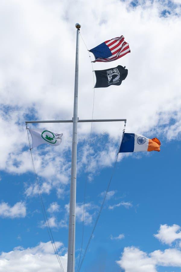 Quatre drapeaux sur un mât de drapeau grand ondulant dans le vent, bannière étoilée, prisonnier de guerre, département de parcs,  image stock