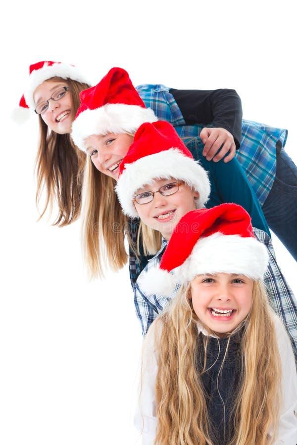 Quatre enfants avec rire de chapeaux de Noël photos stock