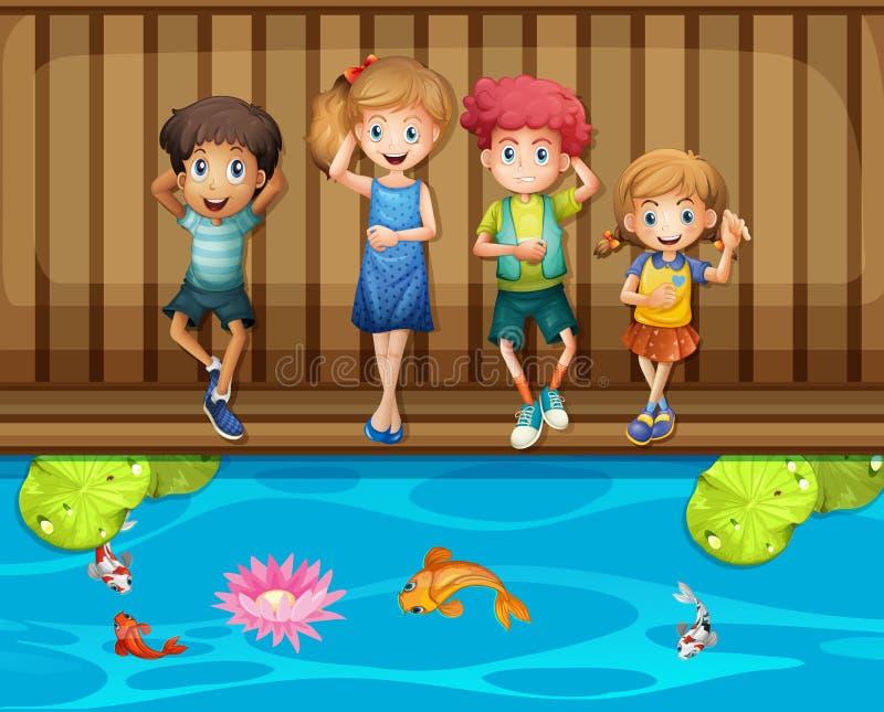 Quatre enfants ayant l'amusement par l'étang à poissons illustration libre de droits