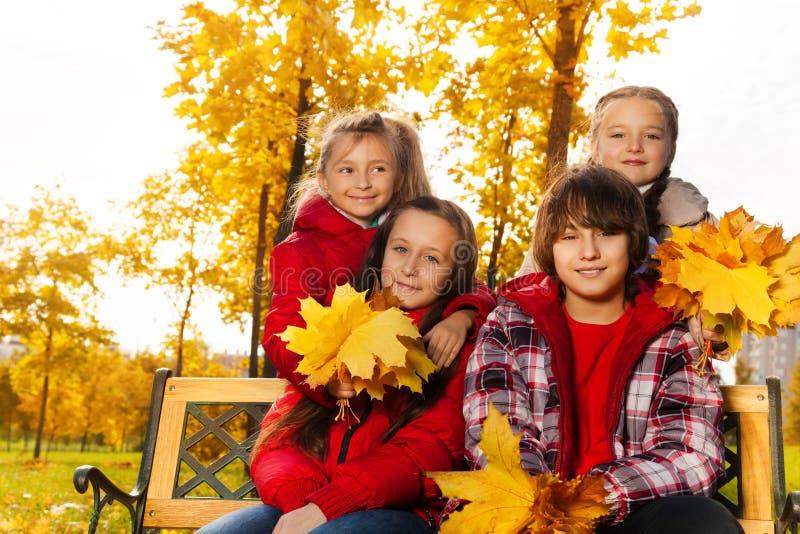 Quatre enfants heureux avec le bouquet d'érable image libre de droits