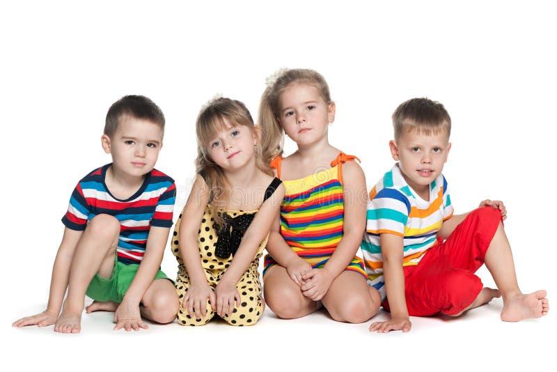 Quatre enfants préscolaires s'asseyent sur le plancher photographie stock
