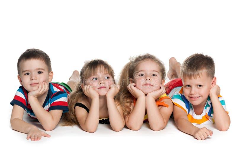 Quatre enfants préscolaires sur le plancher images stock