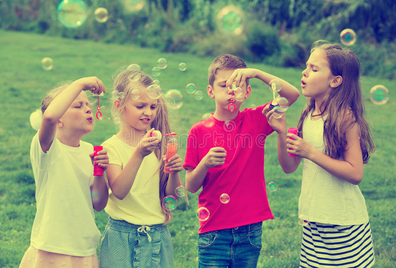 Quatre enfants s'asseyant ensemble et bulles de savon de soufflement photos stock