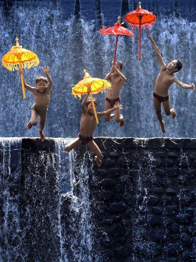 Quatre enfants sautent avec des parapluies photographie stock