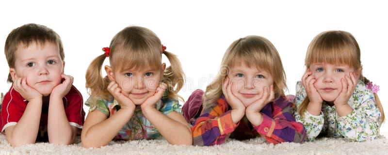 Quatre enfants se trouvant sur le tapis image stock