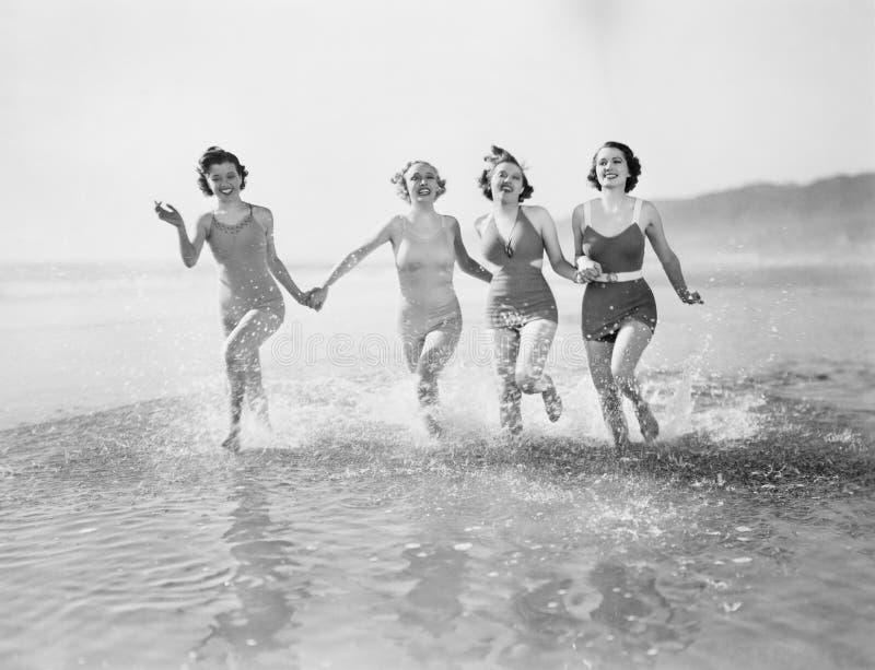 Quatre femmes courant dans l'eau sur la plage (toutes les personnes représentées ne sont pas plus long vivantes et aucun domaine  photographie stock libre de droits