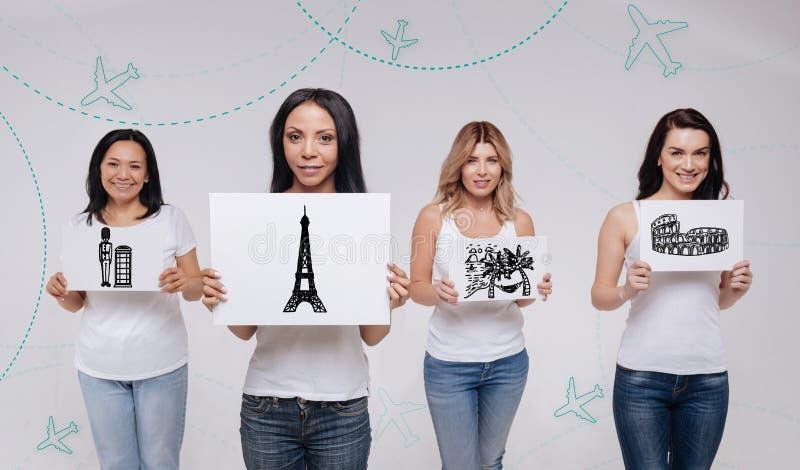 Quatre femmes souriant et rêvant de visiter les endroits célèbres images libres de droits