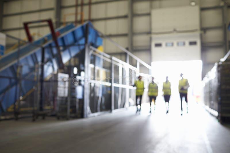 Quatre figures marchant à un foyer intérieur et mou industriel photographie stock libre de droits