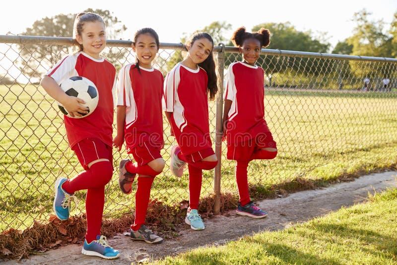 Quatre filles pré de l'adolescence dans une équipe de football regardant à l'appareil-photo photographie stock