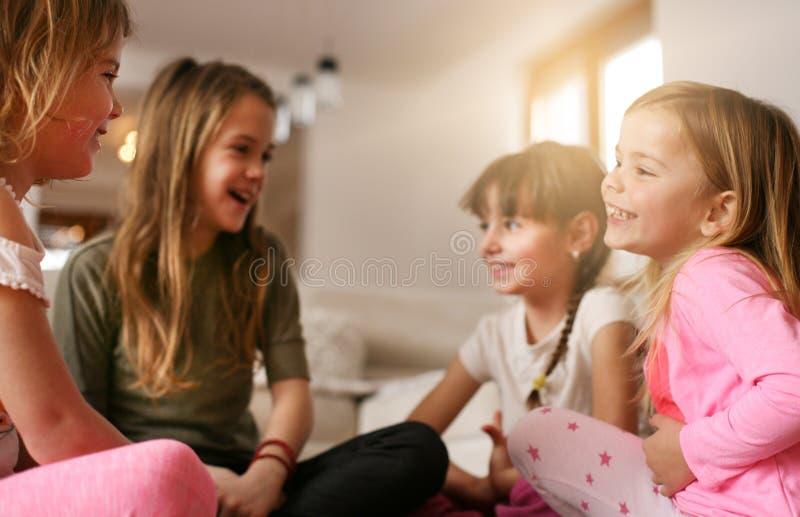 Quatre filles s'asseyant sur le plancher images libres de droits
