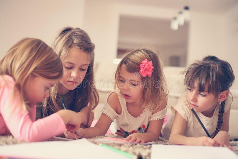 Quatre filles se trouvant sur le plancher photos stock