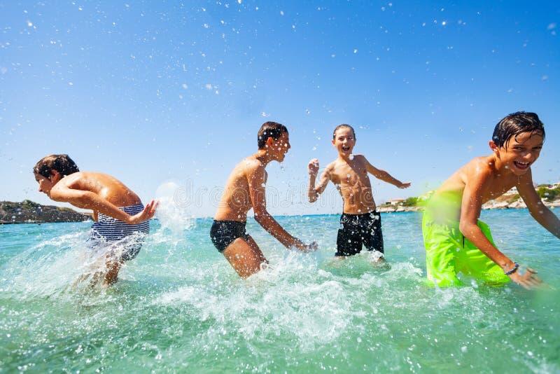 Quatre garçons heureux jouant à l'eau peu profonde tropicale images stock