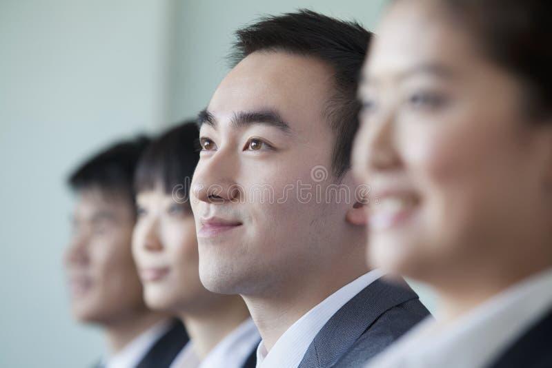 Quatre gens d'affaires s'asseyant dans une rangée, portrait photographie stock