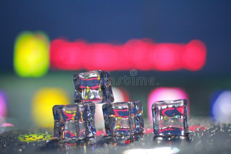 Quatre glaçons et gouttelettes d'eau et lightblur le fond je image libre de droits