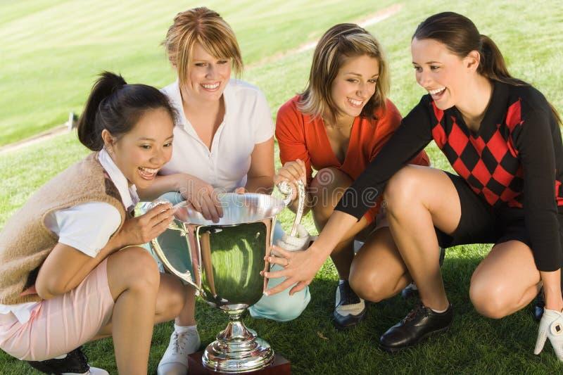 Quatre golfeurs féminins se tapissant autour du trophée photo libre de droits