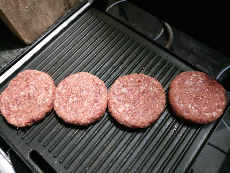 Quatre hamburgers crus de boeuf photographie stock libre de droits