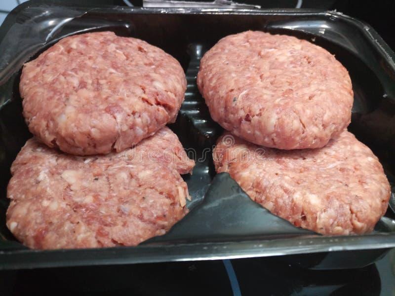 Quatre hamburgers organiques crus ronds de boeuf dans un packge images stock