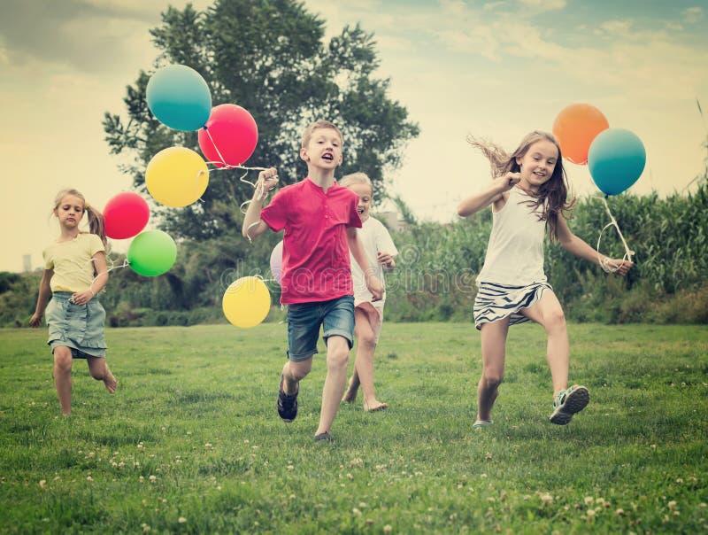 Quatre heureux enfants amicaux courant sur la pelouse verte photographie stock