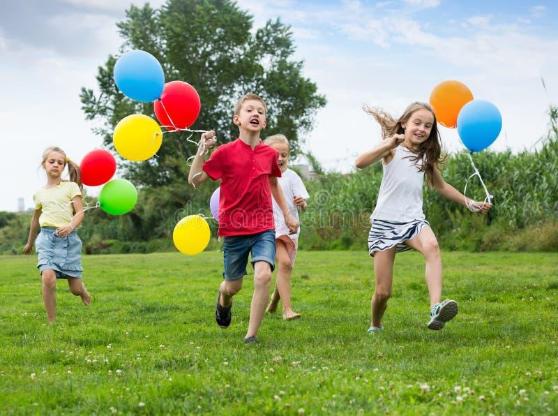 Quatre heureux enfants amicaux courant sur la pelouse verte photos stock