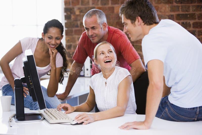 Quatre hommes d'affaires dans des bureaux avec l'ordinateur image libre de droits