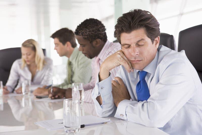 Quatre hommes d'affaires dans la chambre avec un homme en sommeil images stock